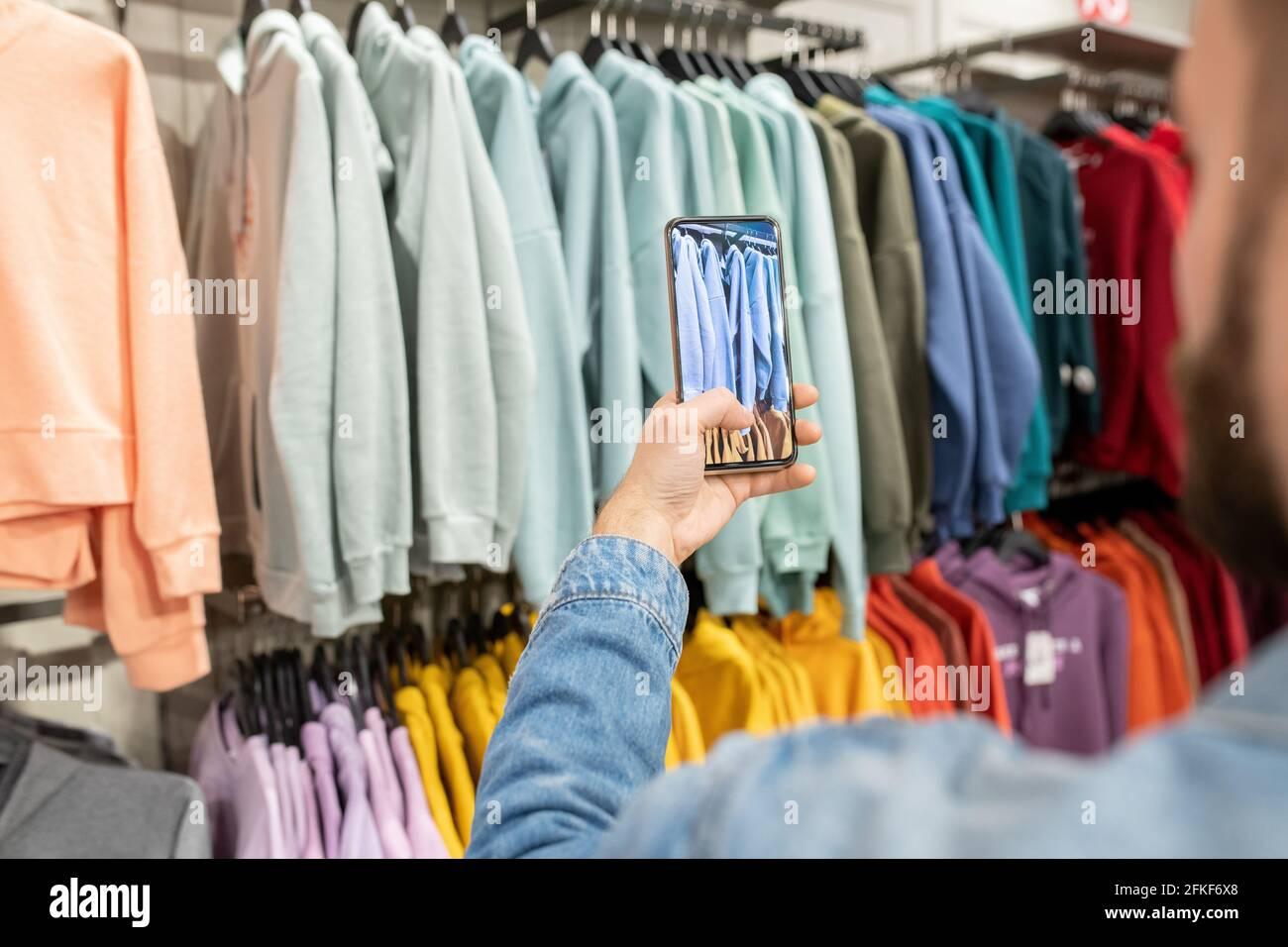 Una persona che scatta foto della nuova collezione di moda durante lo shopping Foto Stock