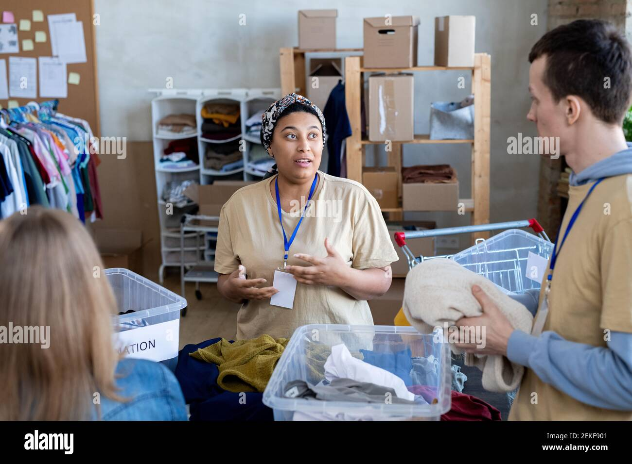 Un gruppo di volontari che parlano e scelgono i vestiti di donazione Foto Stock