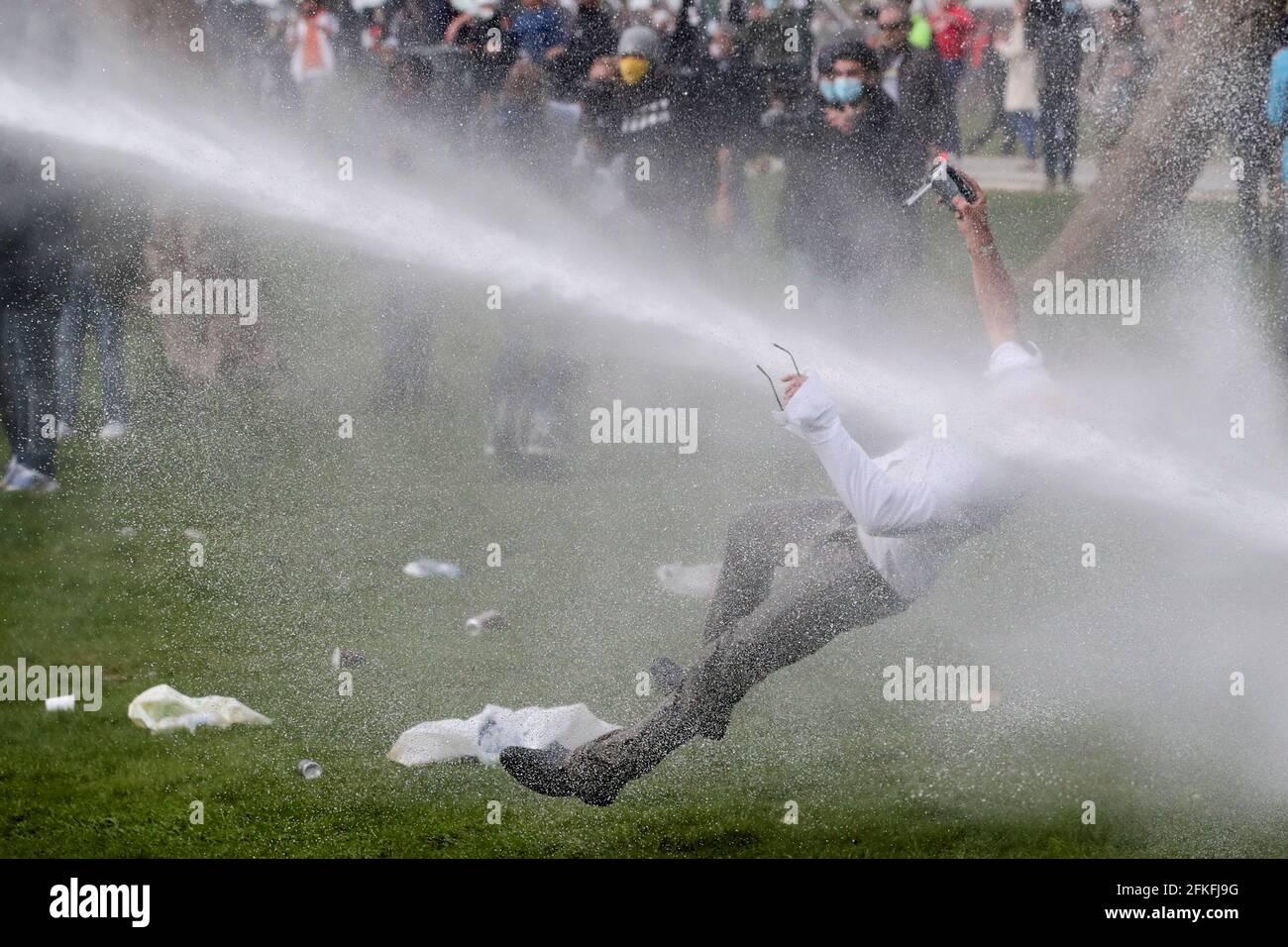 Un uomo è destato da un cannone d'acqua durante gli scontri, mentre la gente si riunisce al parco Bois de la Cambre/Ter Kamerenbos per un partito chiamato 'la Boum 2' in contrasto con la malattia del coronavirus del Belgio (COVID-19) misure di allontanamento sociale e restrizioni, a Bruxelles, Belgio 1 maggio 2021. REUTERS/Yves Herman Foto Stock
