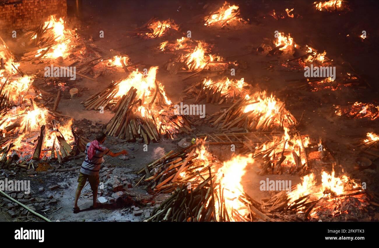 Nuova Delhi, India. 01 Maggio 2021. I lavoratori e i membri della famiglia portano un corpo per la cremazione vicino a più pire funerarie delle vittime di COVID-19 bruciare su un terreno che è stato convertito in un crematorio per la cremazione di massa a Nuova Delhi, India il Sabato, 1 maggio 2021. Foto di Abhishek/UPI Credit: UPI/Alamy Live News Foto Stock