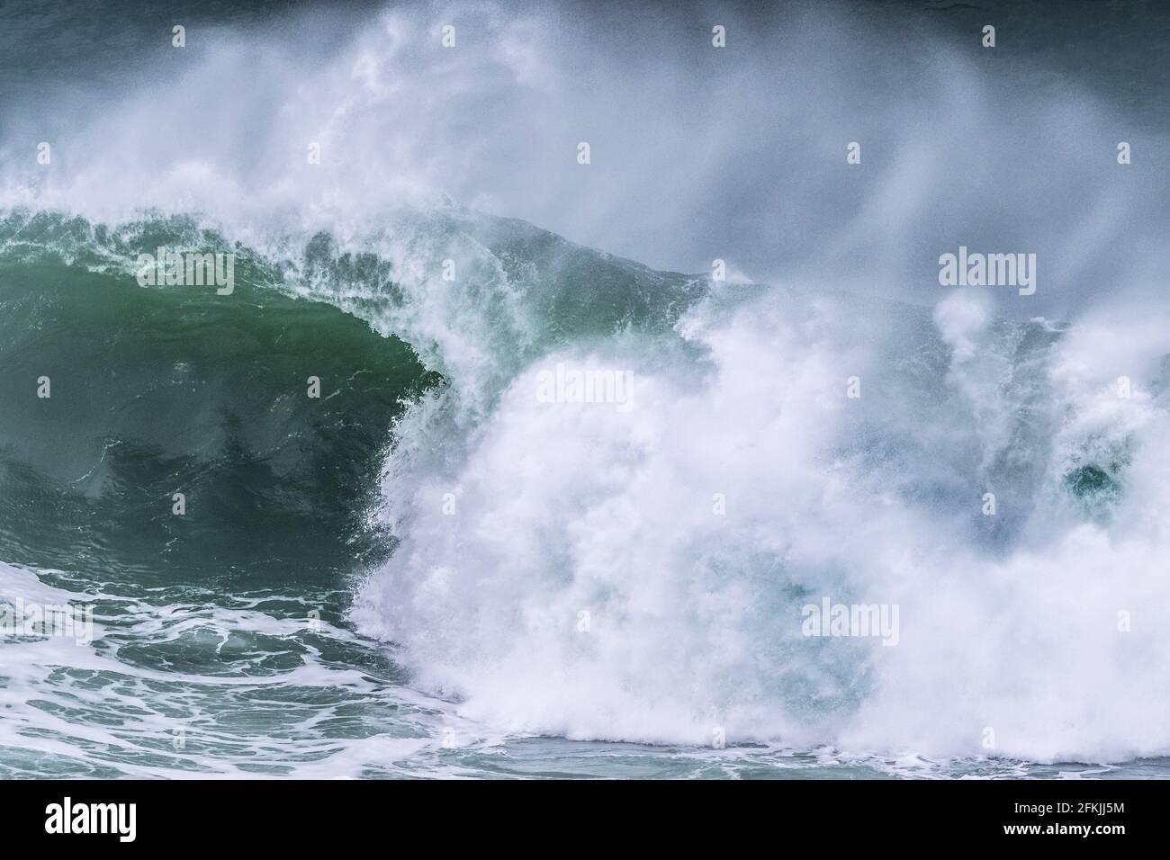 Un'onda selvaggia che si infrana sulla barriera corallina di Cribbar al largo di Towan Head a Newquay in Cornovaglia. Foto Stock