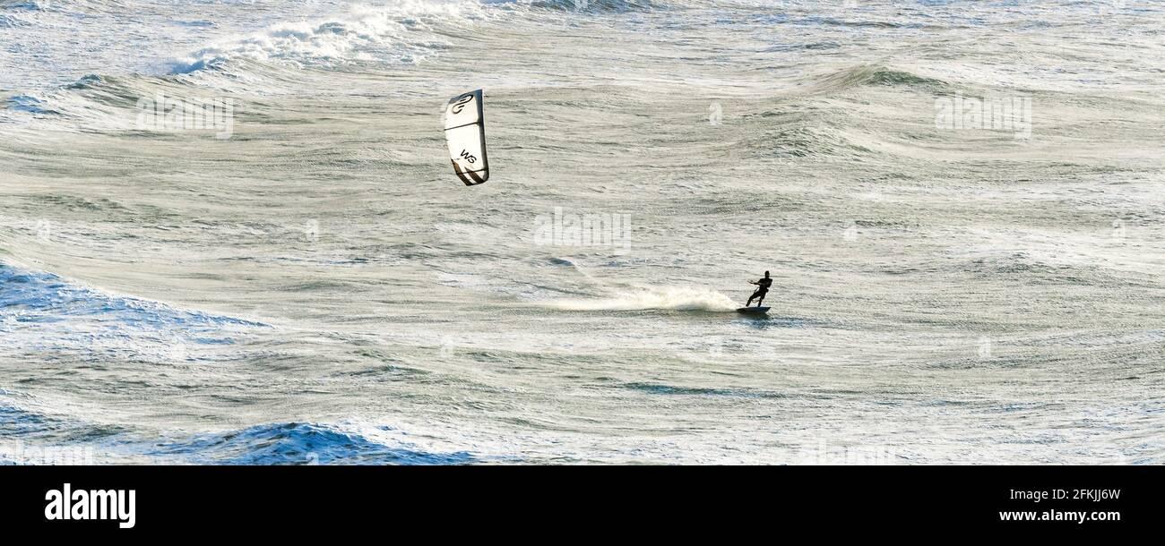 Un'immagine panoramica di un kite surfer che cavalca le onde in alto vento alla spiaggia di Crantock a Newquay in Cornovaglia. Foto Stock