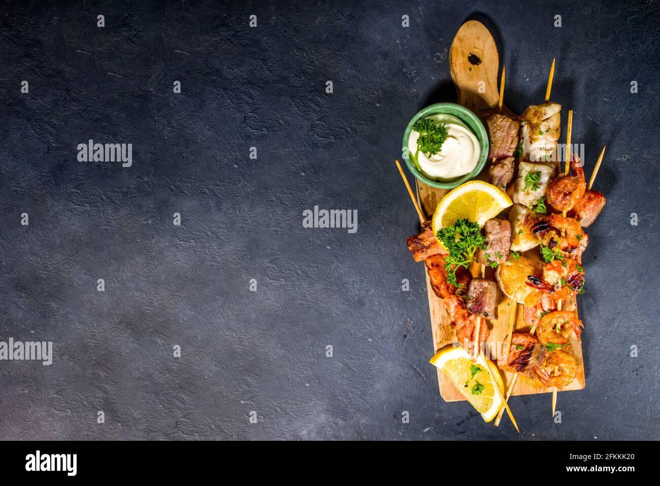 Assortimento barbecue vari piatti mediterranei alla griglia - pesce, gamberi, granchio, cozze, kebab con salse, sfondo nero in calcestruzzo, sopra lo spazio di copia Foto Stock