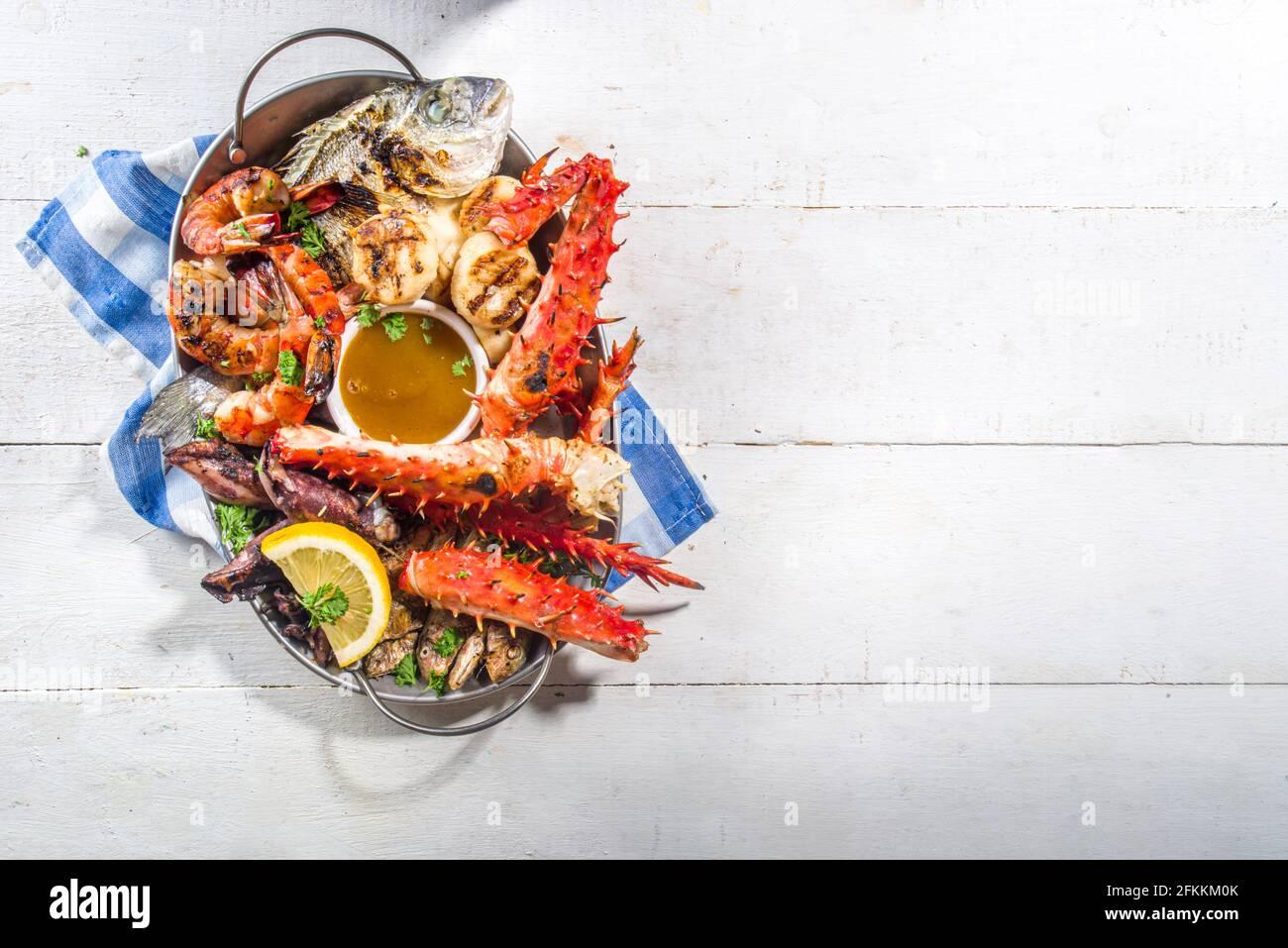 Assortimento barbecue vari piatti mediterranei alla griglia - pesce, polpo, gamberi, granchio, frutti di mare, cozze, dieta estiva festa barbecue, con kebab, salse, Foto Stock