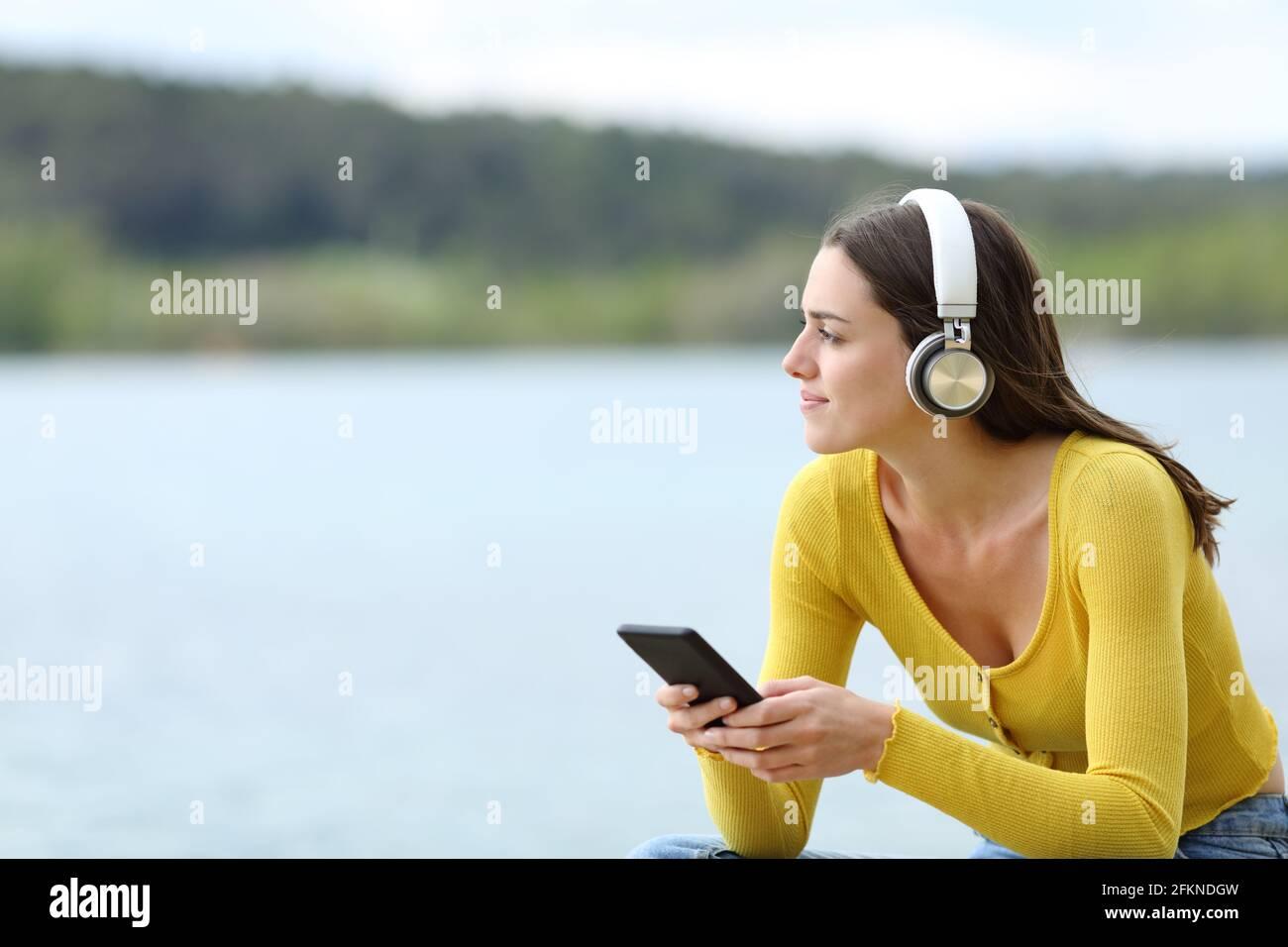 Donna soddisfatta che ascolta la musica con le cuffie wireless che guardano lontano in un lago Foto Stock