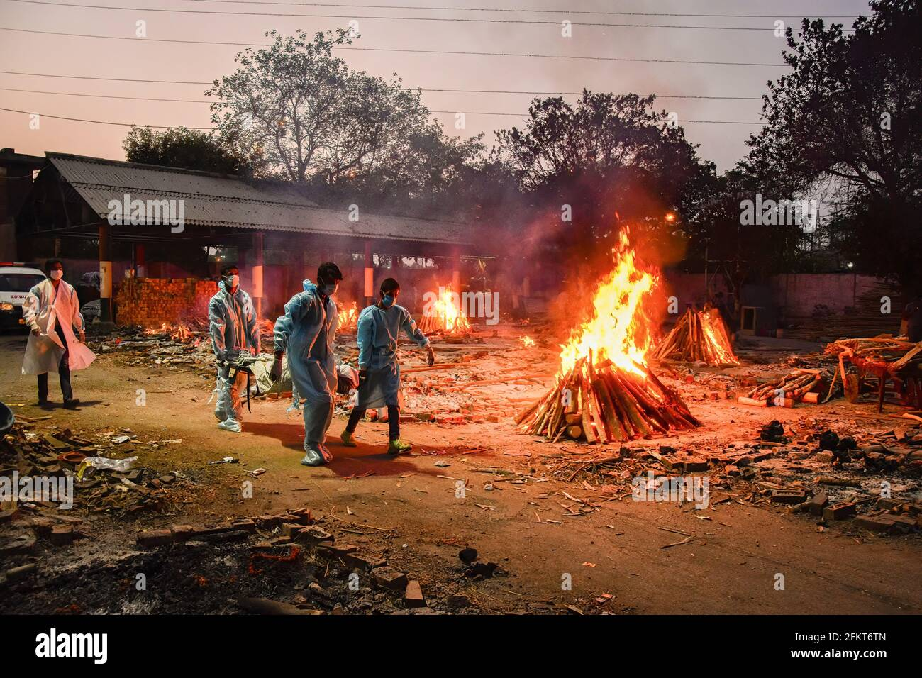 Nuova Delhi, India. 03 maggio 2021. (NOTA REDATTORI: Immagine raffigurante la morte)i lavoratori portano il corpo di una persona che è morto della malattia del coronavirus di Covid-19 come altre pire funerali sono viste bruciare durante una cremazione di massa tenuta ad un crematorio. L'India ha registrato un totale di 19.9 milioni di casi e 219,000 decessi dall'inizio dell'epidemia. Credit: SOPA Images Limited/Alamy Live News Foto Stock