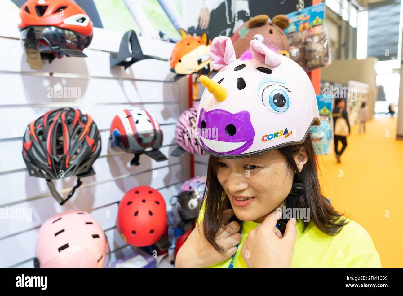 Shanghai. 5 maggio 2021. Un membro dello staff mostra un casco a forma di cartoni animati durante la 30esima Fiera Internazionale della bicicletta della Cina a Shanghai, 5 maggio 2021. L'evento della durata di quattro giorni è iniziato mercoledì, attirando oltre 1,000 aziende a partecipare. Credit: CAI Yang/Xinhua/Alamy Live News Foto Stock