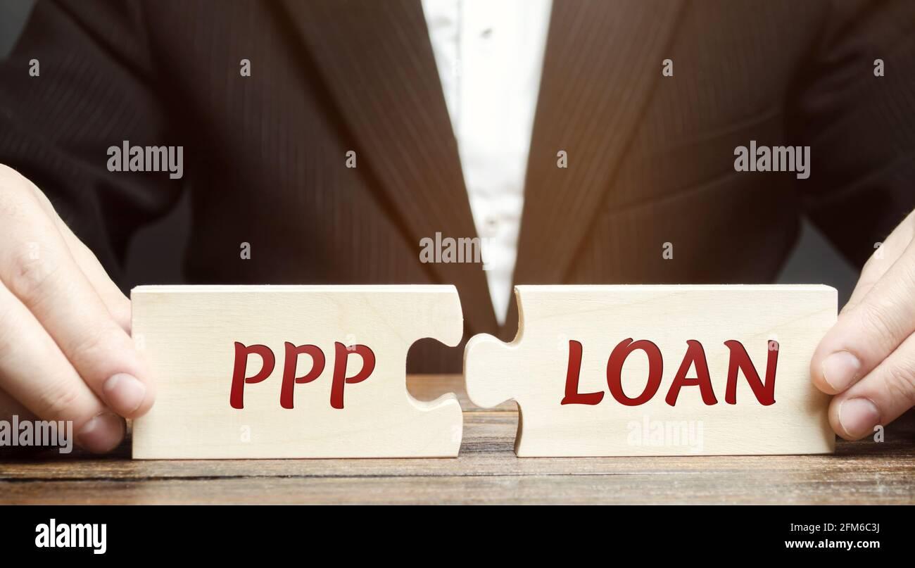 Businessman mette puzzle con parole prestito PPP - Paycheck Protection Program. Prestito progettato per fornire un incentivo diretto per le piccole imprese a tenere t Foto Stock