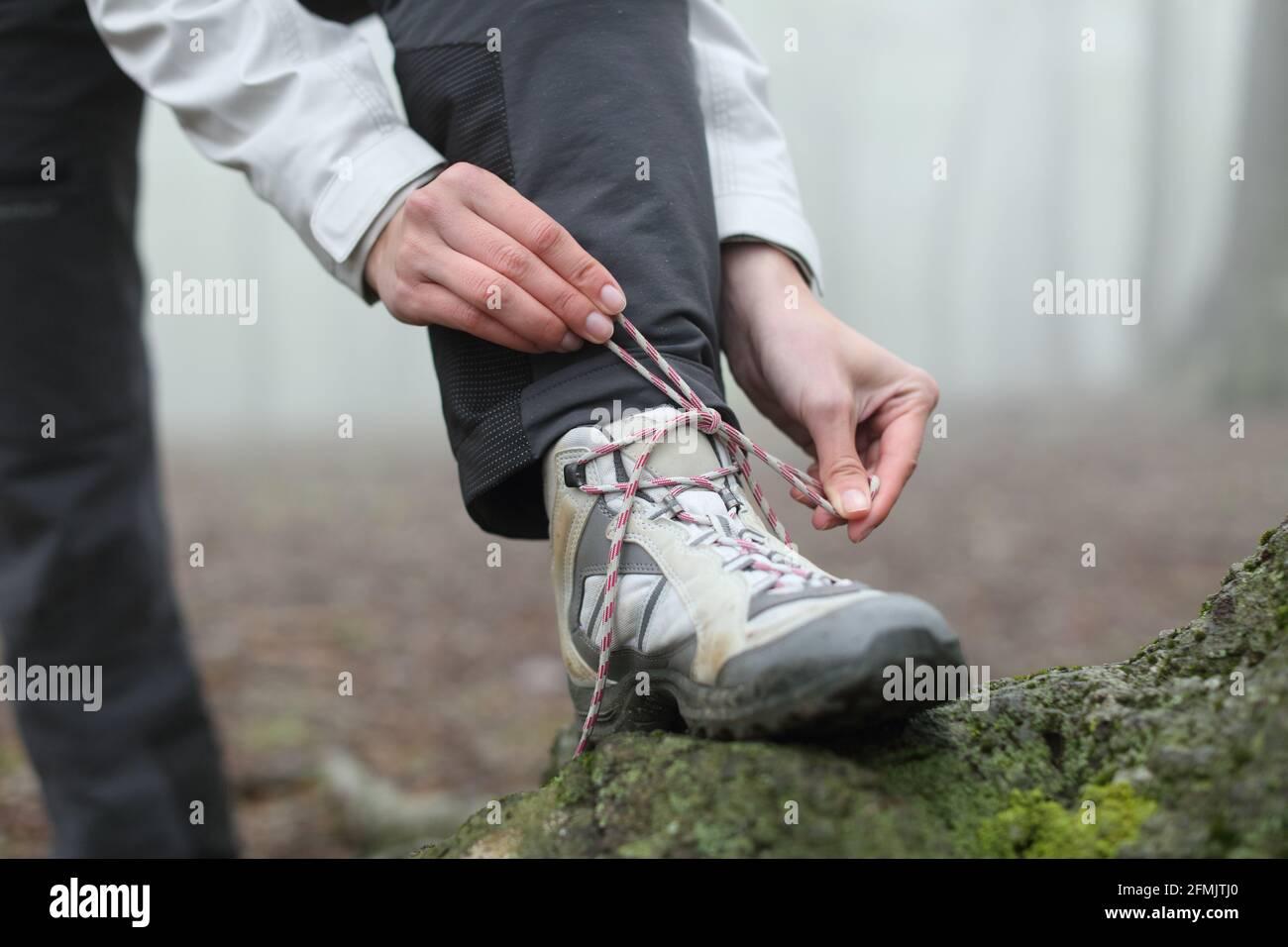 Primo piano di un escursionista mani legando i lacci di stivale in la montagna Foto Stock