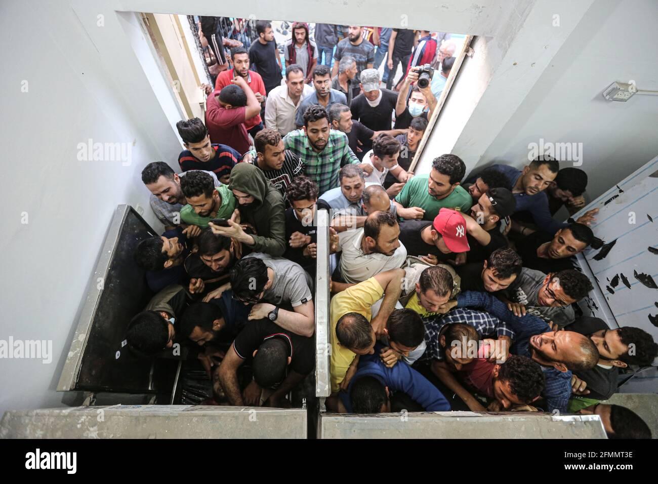 Gaza. 10 maggio 2021. I palestinesi si riuniscono attorno a corpi di palestinesi uccisi durante un attacco aereo israeliano in un ospedale di guerra nella striscia di Gaza settentrionale, il 10 maggio 2021. Israele ha effettuato attacchi aerei nella striscia di Gaza, uccidendo almeno 20 persone, mentre il fuoco a razzo dall'enclave palestinese è continuato fino a lunedì sera, secondo fonti israeliane e palestinesi. Credit: Rizek Abdeljawad/Xinhua/Alamy Live News Foto Stock