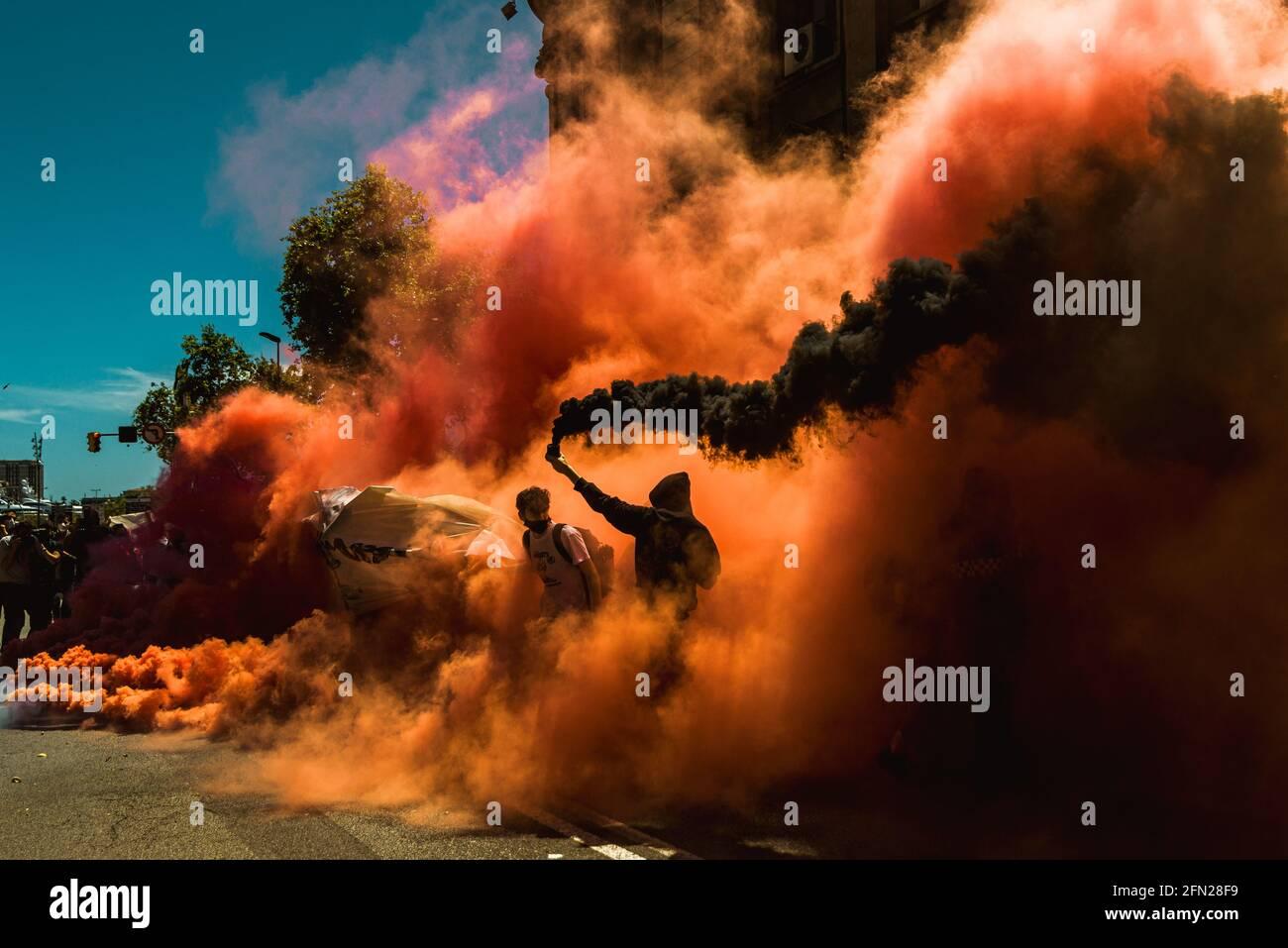 Barcellona, Spagna. 13 maggio 2021. Colpendo gli studenti catalani si accendono gli incendi del Bengala mentre protestano contro la crisi educativa durante la continua diffusione del virus corona. Credit: Matthias Oesterle/Alamy Live News Foto Stock