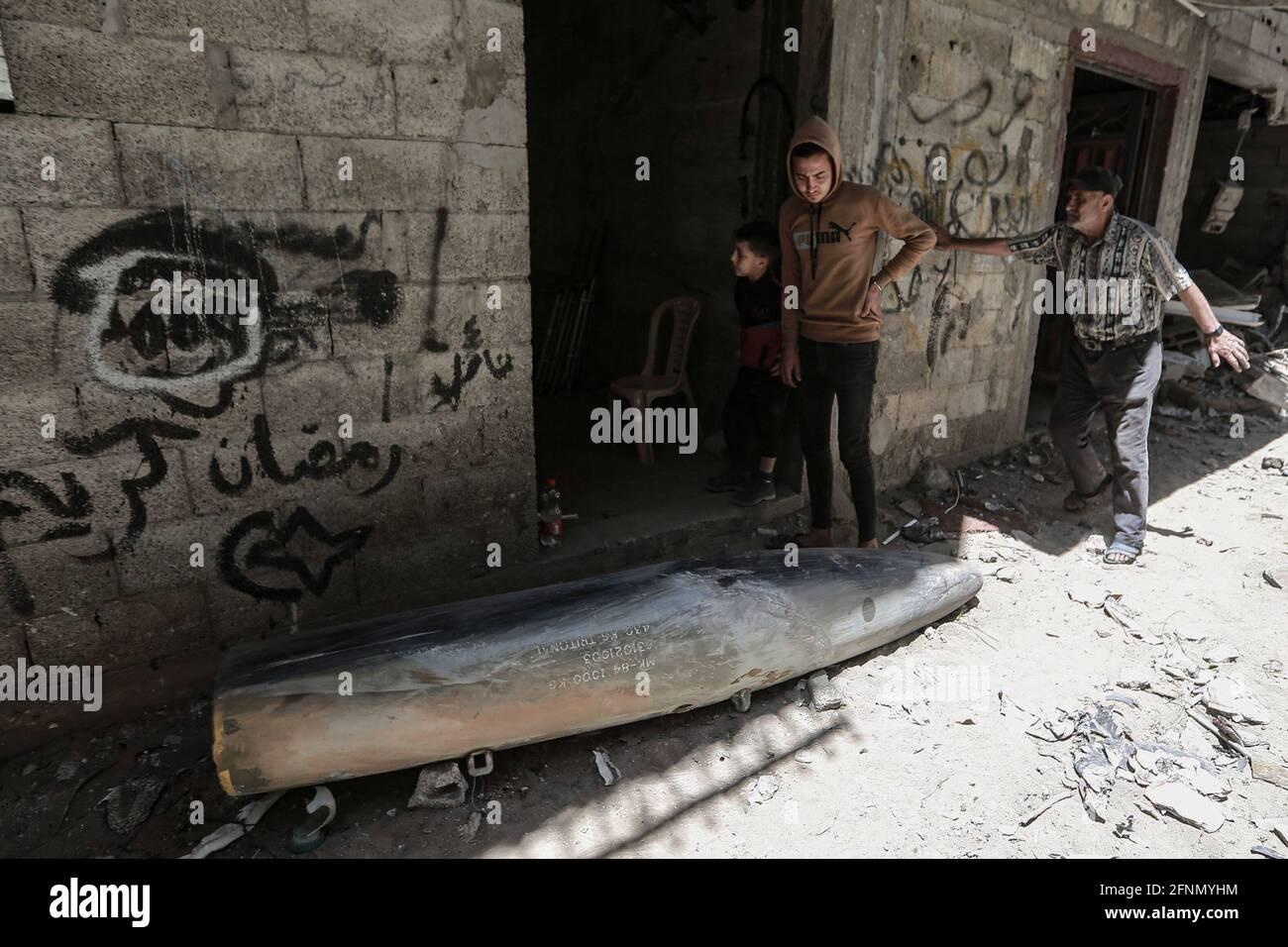 Gaza, territori palestinesi. 18 maggio 2021. I palestinesi ispezionano una bomba inesplosa caduta da un aereo da guerra israeliano F-16 nel quartiere di Rimal, in mezzo all'escalation della violenza israelo-palestinese. Credit: Mohammed Talatene/dpa/Alamy Live News Foto Stock