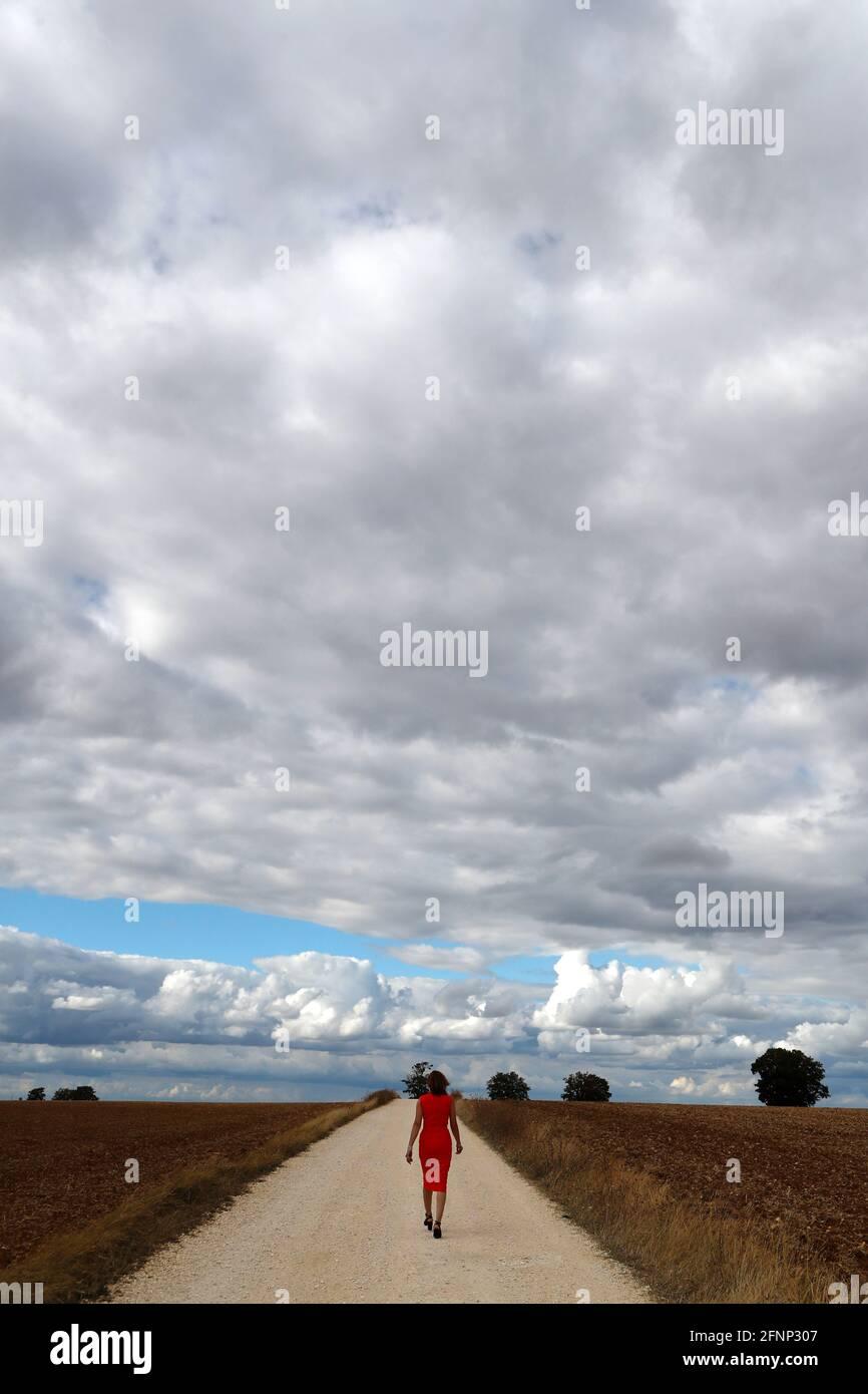 Vista posteriore di una donna che cammina da sola su una strada di campagna rettilinea. Cielo nuvoloso. Francia. Foto Stock