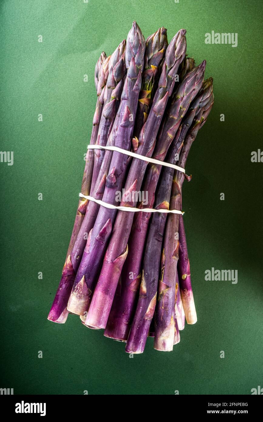 Mazzo fresco di asparagi organici crudi, verdure viola, verdi e bianche su sfondo verde scuro Foto Stock