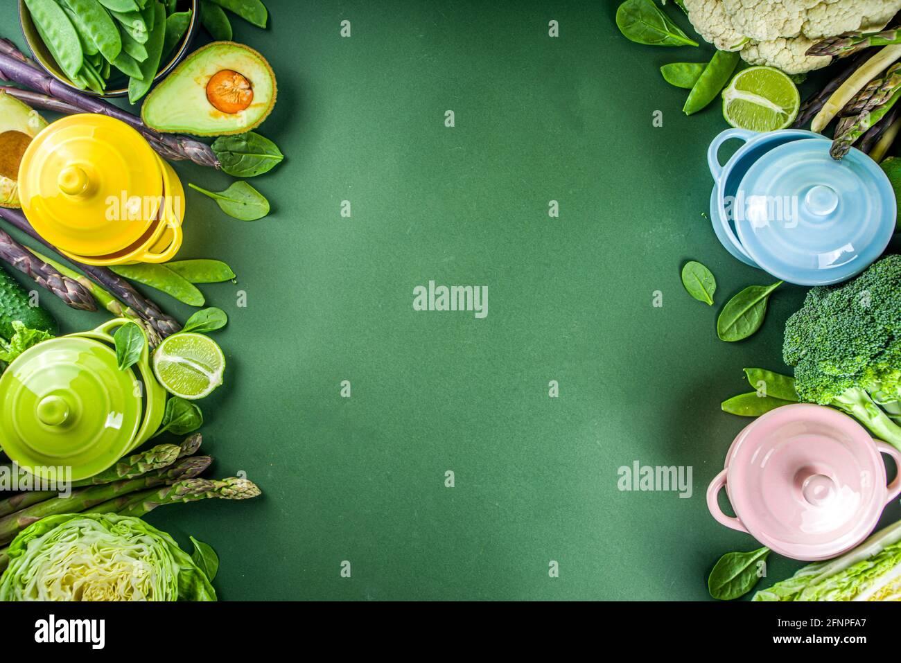 Vari ingredienti vegetali di primavera verdi organici con pentole da cucina vuote e colorate su un tavolo da cucina verde scuro, vista dall'alto. Dieta zuppa sana Foto Stock