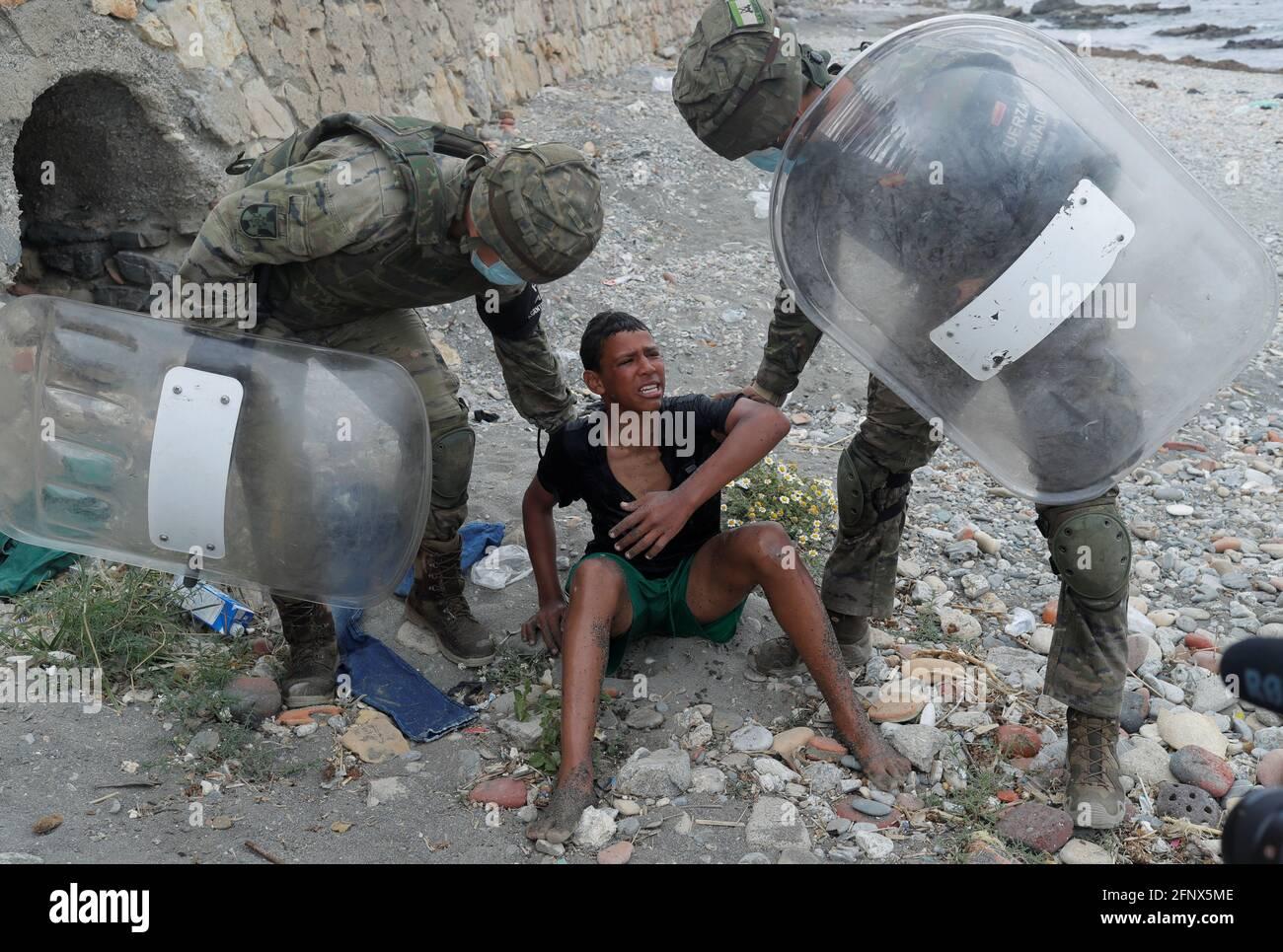 Soldati spagnoli assistono un migrante alla spiaggia di El Tarajal, vicino alla recinzione tra il confine spagnolo-marocchino, dopo che migliaia di migranti hanno attraversato il confine, a Ceuta, Spagna, 19 maggio 2021. REUTERS/Jon Nazca Foto Stock