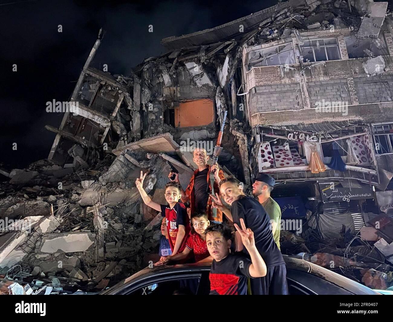 La gente si avvicina alle macerie di un edificio danneggiato mentre i palestinesi celebrano nelle strade dopo un cessate il fuoco, a Gaza City 21 maggio 2021. REUTERS/Mohammed Salem Foto Stock