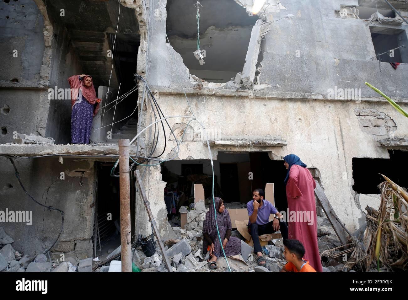 I palestinesi si siedono sui detriti dopo il ritorno alla loro casa distrutta dopo la tregua di Israele-Hamas, a Beit Hanoun, nella striscia di Gaza settentrionale, il 21 maggio 2021. REUTERS/Mohammed Salem Foto Stock