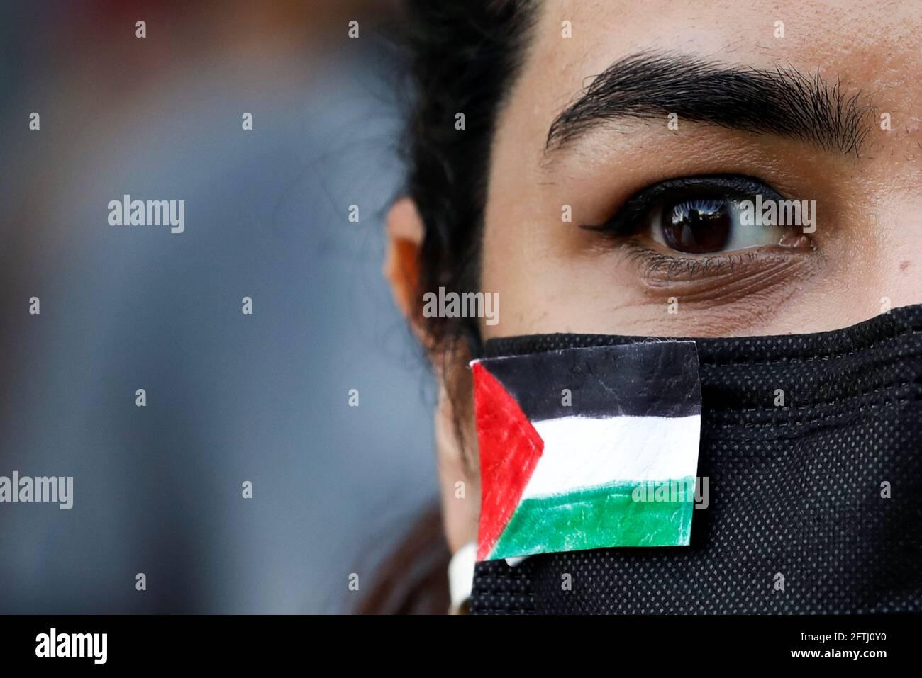 Una donna indossa una bandiera palestinese sulla sua maschera protettiva per esprimere solidarietà al popolo palestinese e protestare contro Israele, durante un raduno a Karachi, Pakistan, il 21 maggio 2021. REUTERS/Akhtar Soomro Foto Stock