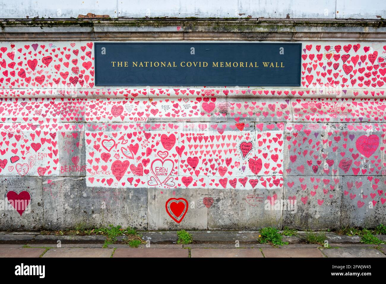 National Covid Memorial Wall in una giornata di lavoro a Lambeth, Londra, Regno Unito. Cuori rossi disegnati su un muro che rappresenta ogni morte di COVID 19. Erbacce Foto Stock