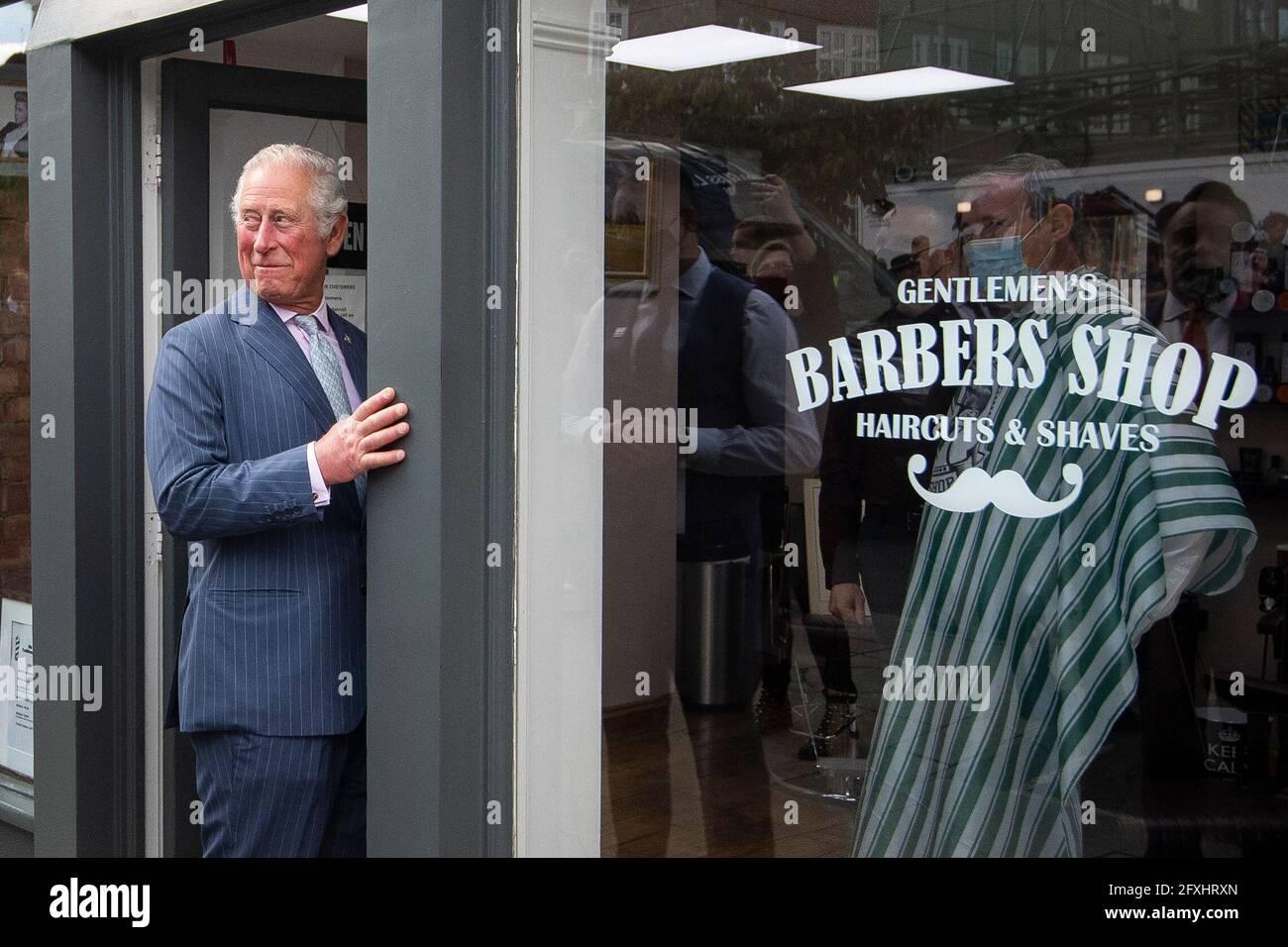Il Principe del Galles si trova all'ingresso di un negozio di barbiere, mentre il Principe del Galles e la Duchessa di Cornovaglia visitano la Citta' Vecchia di Clapham a Londra per celebrare il settore delle strade e dei negozi al dettaglio come negozi non essenziali riaperti e le restrizioni di Coronavirus sono facili. Data immagine: Giovedì 27 maggio 2021. Foto Stock