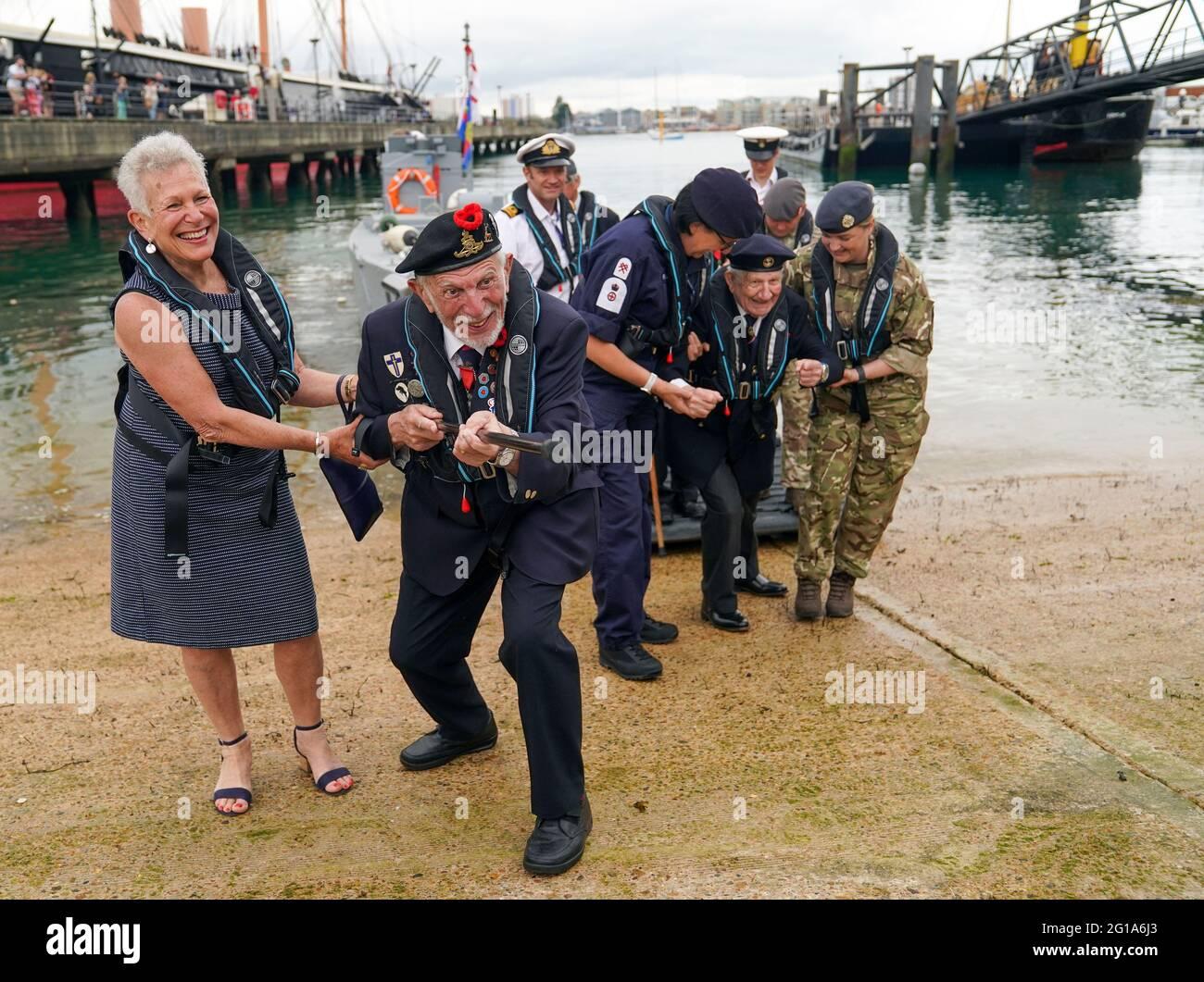 Joe Cattini, veterano del D-Day, solleva il suo bastone da passeggio come una mitragliatrice, mentre lui e altri veterani sono accolti nel porto storico di Portsmouth per commemorare il 77° anniversario degli sbarchi in Normandia. Data immagine: Domenica 6 giugno 2021. Foto Stock