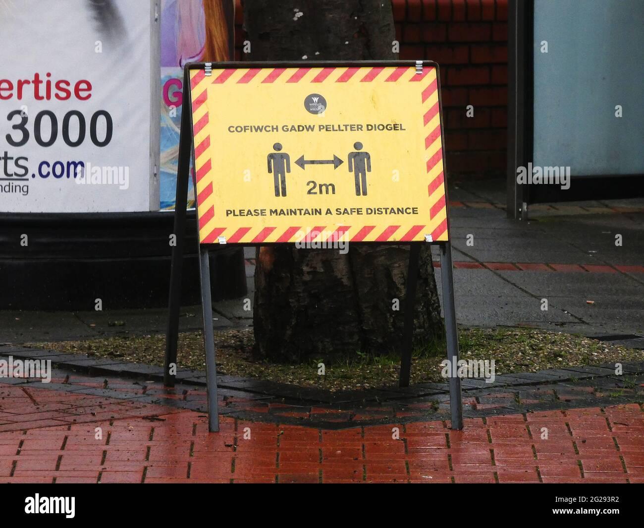Coronavirus Covid 19 - segnali di avvertimento nel centro di Wrexham durante la pandemia. Segno di allontanamento sociale Foto Stock