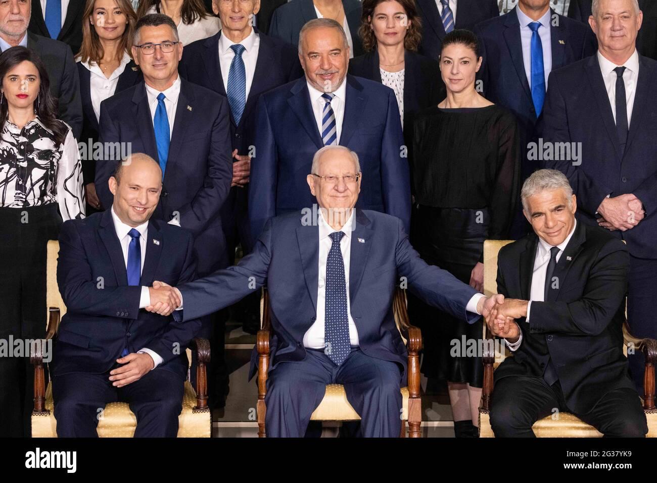 (210614) -- GERUSALEMME, 14 giugno 2021 (Xinhua) -- Il nuovo primo ministro israeliano Naftali Bennett (L, prima fila), il presidente israeliano Reuven Rivlin (C, prima fila) e il primo ministro e ministro degli Esteri alternativo Yair Lapid (R, prima fila) propongono una foto di gruppo con i nuovi ministri del governo nella residenza del presidente a Gerusalemme, 14 giugno 2021. (JINI via Xinhua) Foto Stock