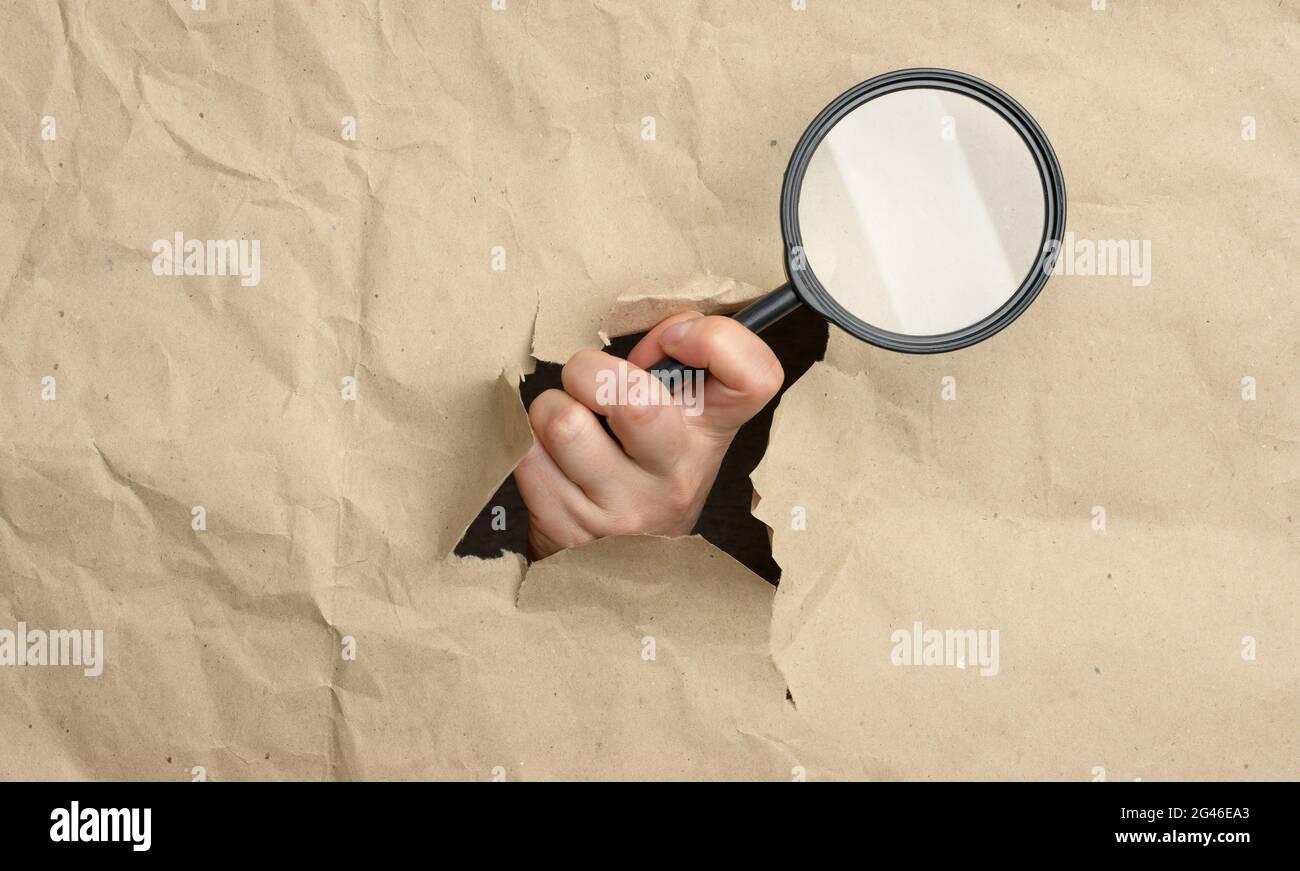 La mano di una donna tiene una lente di ingrandimento di vetro, una parte del corpo sporge da un foro in carta marrone Foto Stock