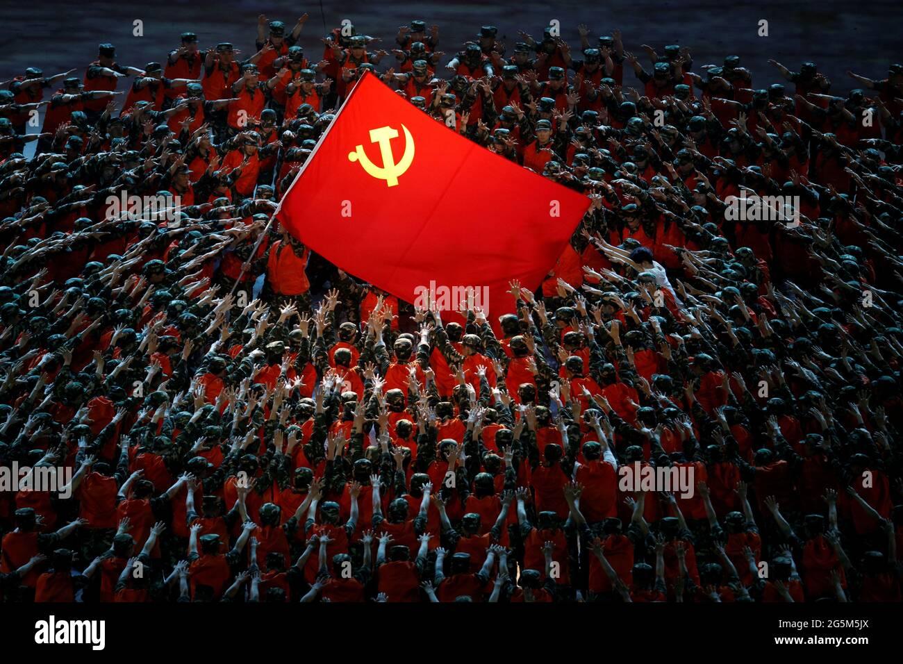 Gli artisti si esibiscono intorno alla bandiera rossa durante uno spettacolo commemorativo del centesimo anniversario della fondazione del Partito comunista cinese allo Stadio Nazionale di Pechino, Cina, 28 giugno 2021. REUTERS/Thomas Peter Foto Stock