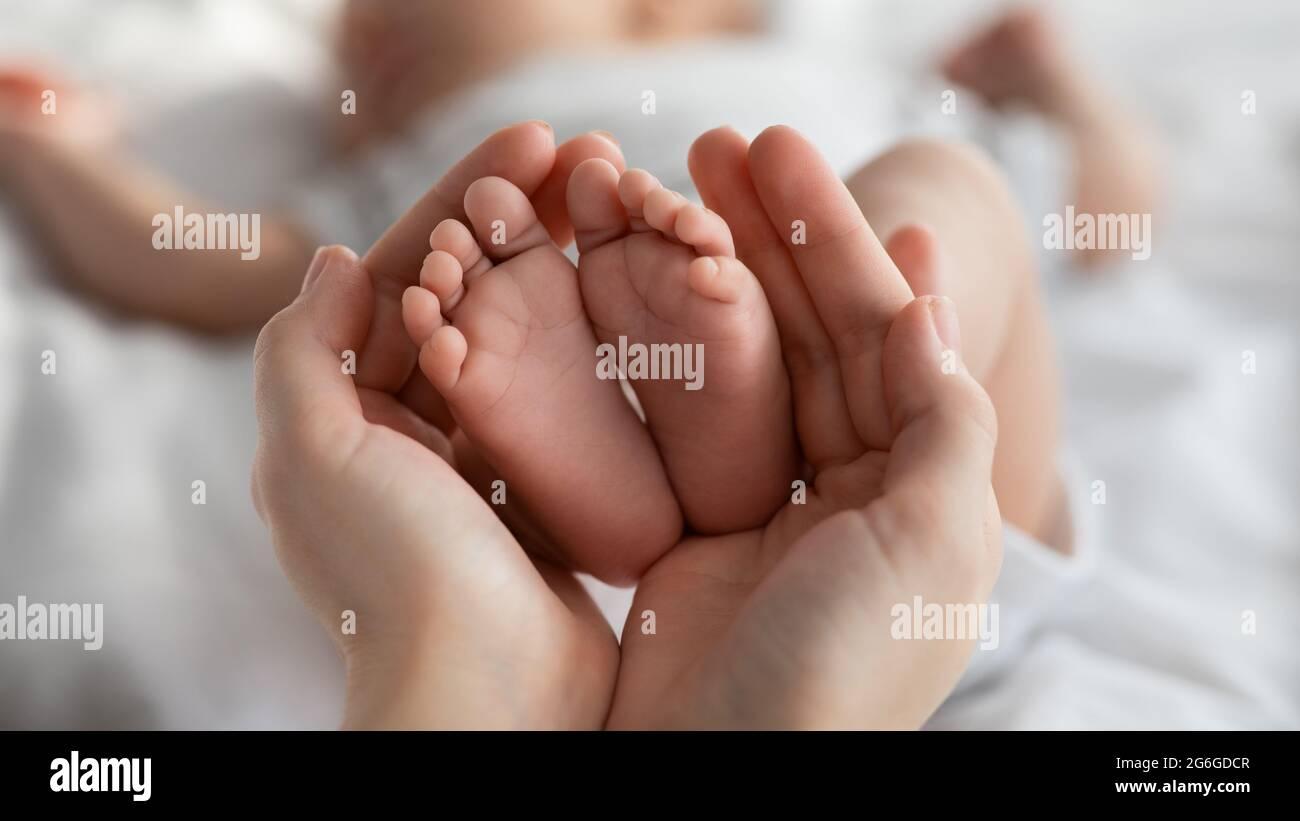 Primo piano dei piccoli piedi del neonato nelle mani della mamma Foto Stock