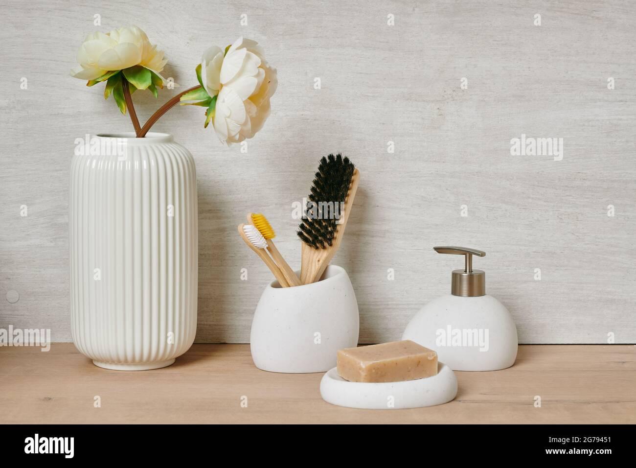 Gruppo di articoli per la cura del corpo contro la parete bianca in bagno Foto Stock