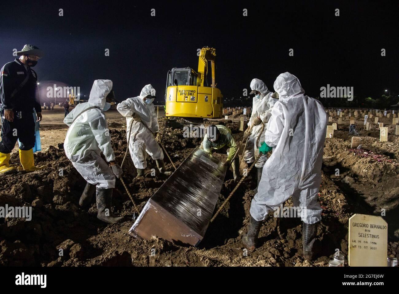 Giacarta, Indonesia. 13 luglio 2021. Gli scavatori della tomba lavorano durante la sepoltura di una vittima di coronavirus COVID-19 in un cimitero speciale. L'Indonesia ha registrato oltre 2,600,000 casi di coronavirus (malattia di COVID-19) dall'inizio della pandemia. Credit: Afriadi Hikmal/ZUMA Wire/Alamy Live News Foto Stock