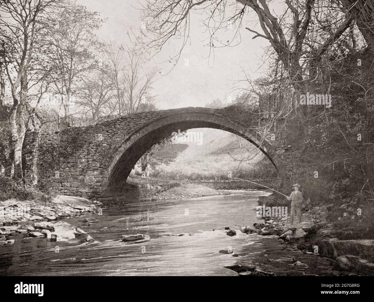 Una vista del tardo 19 ° secolo di un pescatore sotto il 'Ponte Romano' sul fiume Mousemill appena a ovest di Lanark, una città nella cintura centrale della Scozia. Probabilmente il Mousemill Bridge, menzionato per la prima volta nel 1587. Il ponte di pietra che si erge oggi sembra essere stato costruito e sostituito con una struttura in legno intorno al 1649. All'inizio del 19 ° secolo il moderno ponte è stato costruito a pochi metri di distanza e il vecchio permesso di cadere in decadimento. Così probabilmente di dubbia eredità romana! Foto Stock