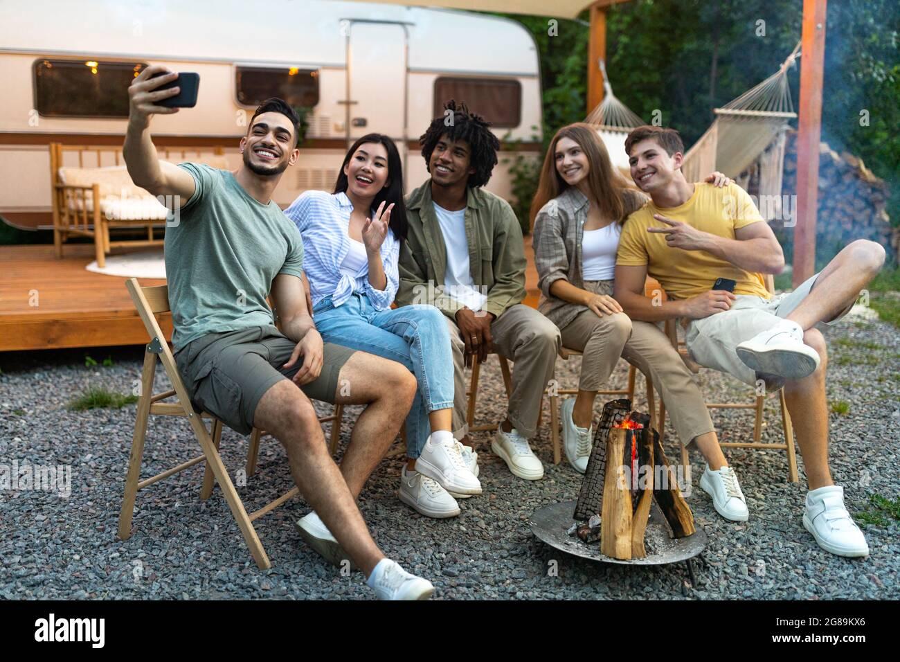 Diversi giovani amici che prendono selfie vicino al fuoco di sera, utilizzando smartphone, seduti accanto al camper durante il viaggio in campeggio Foto Stock