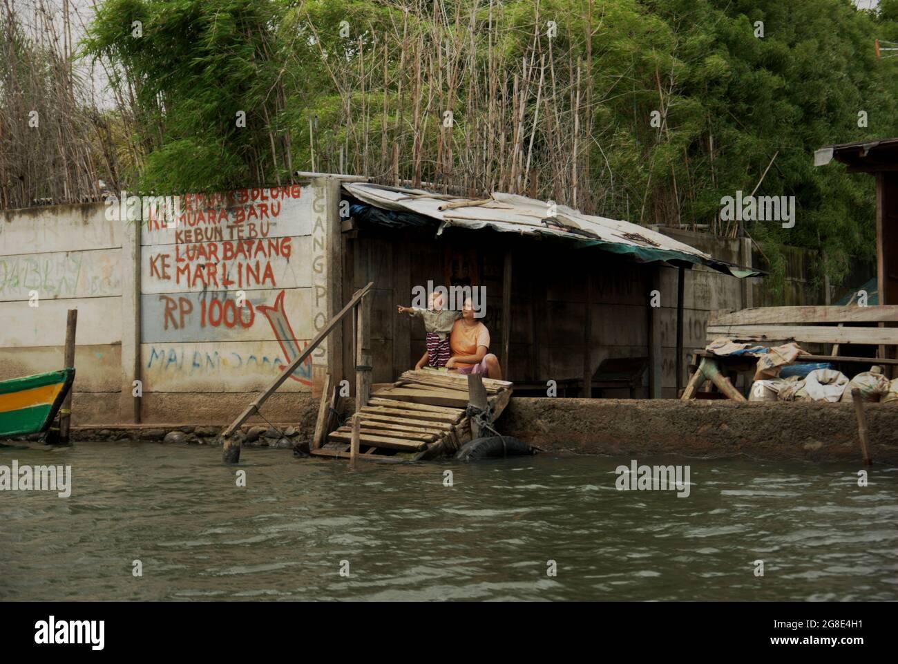 Una donna e un bambino in un terminal di trasporto in barca che collega gli insediamenti costieri con il porto di Sunda Kelapa nella zona costiera di Giacarta, Indonesia. Foto Stock