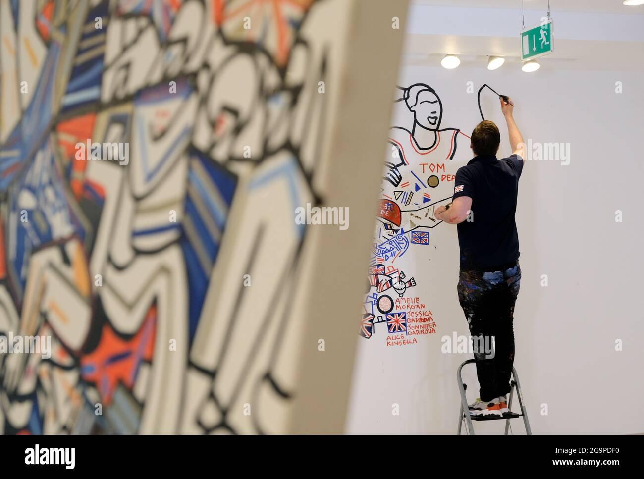 Carnaby Street, Londra, Regno Unito. 27 luglio 2021. Ben Mosley un artista ufficiale della squadra GB sta dipingendo un murale della squadra GB in uno spazio di negozio su Carnaby Street a Londra. Credit: Matthew Chpicle/Alamy Live News Foto Stock