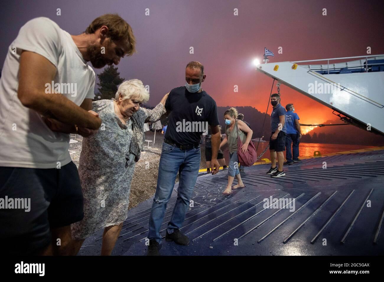 La gente saluta a bordo di un traghetto durante l'evacuazione come un fuoco selvatico brucia nel villaggio di Limni, sull'isola di Evia, Grecia, 6 agosto 2021. Foto scattata il 6 agosto 2021. REUTERS/Nicolas Economou Foto Stock