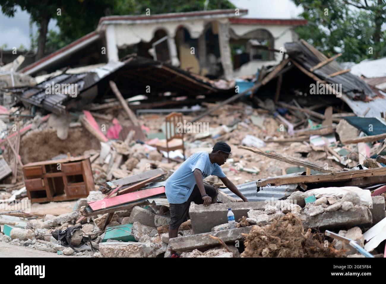 Les Cayes, Haiti. 16 agosto 2021. Un uomo cerca i detriti di una casa collassata dopo un terremoto, a Les Cayes, Haiti, il 16 agosto 2021. Il bilancio delle vittime del potente terremoto che ha colpito Haiti sudoccidentale sabato è salito a 1,419, le autorità hanno annunciato lunedì. Il terremoto di 7.2 magnitudo ha anche causato almeno 6,900 feriti e distrutto oltre 37,000 case, secondo l'agenzia di protezione civile del paese. Credit: David de la Paz/Xinhua/Alamy Live News Foto Stock