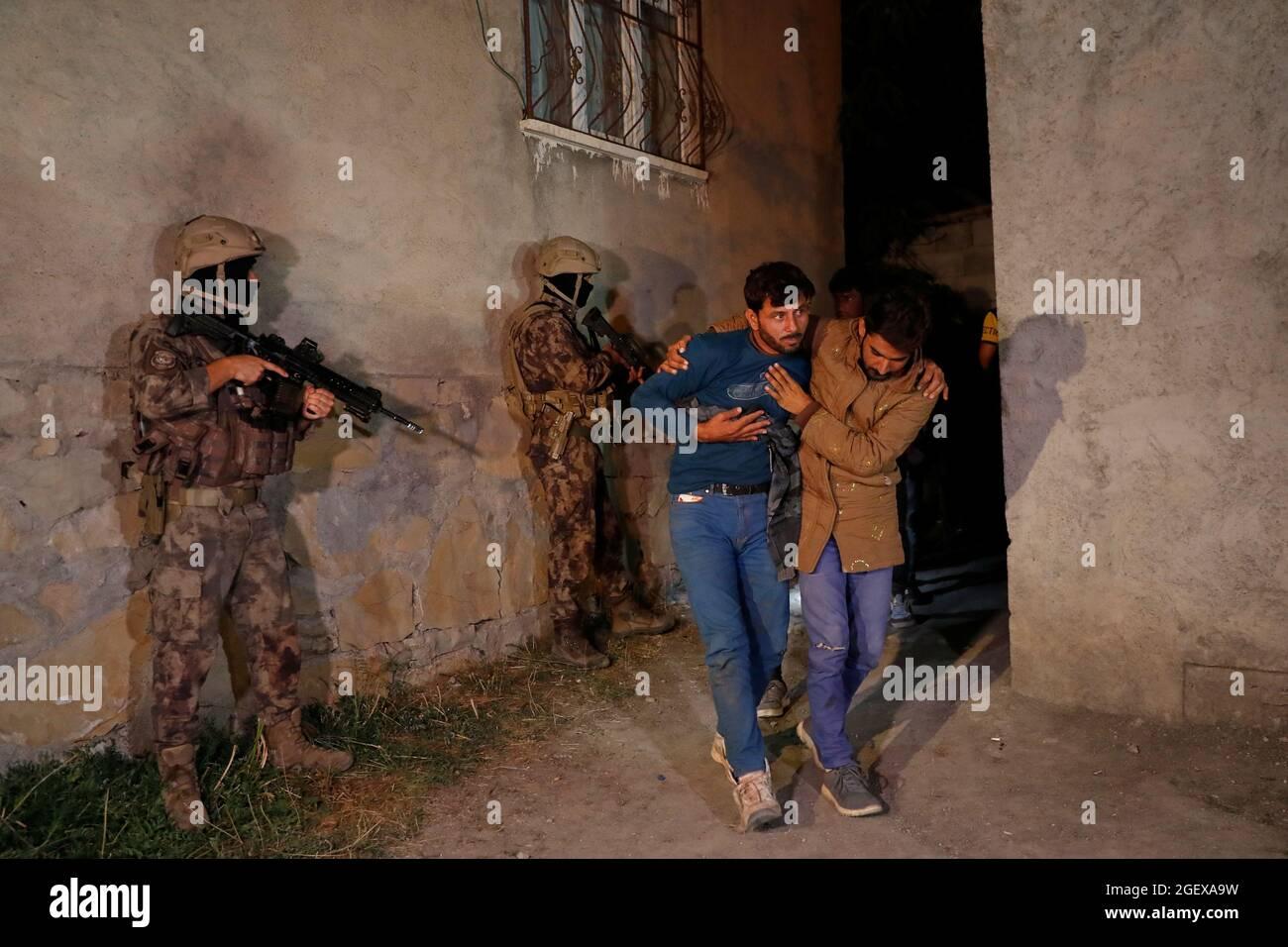 I migranti, principalmente provenienti dall'Afghanistan, sono visti dopo essere stati detenuti dalle forze di sicurezza turche durante un'operazione nella città di confine di Van, Turchia, alla fine del 21 agosto 2021. REUTERS/Murad Sezer Foto Stock