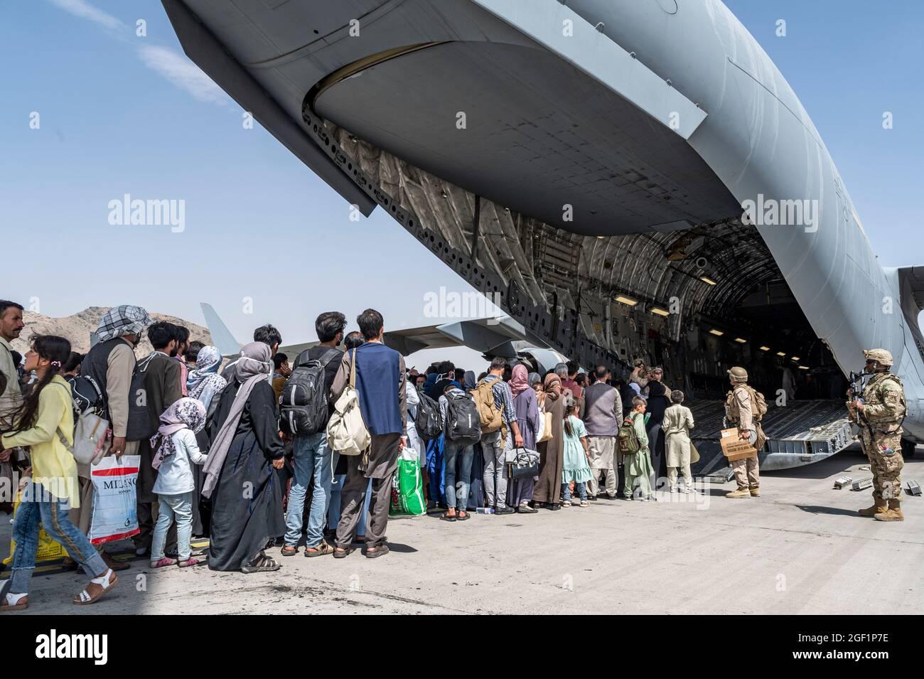 Gli Stati Uniti Airmen e la guida dei marines degli Stati Uniti hanno qualificato gli evacuati a bordo di una forza aerea degli Stati Uniti C-17 Globemaster III a sostegno dell'evacuazione dell'Afghanistan all'aeroporto internazionale Hamid Karzai (HKIA), Afghanistan, 21 agosto 2021. Il Dipartimento della Difesa si impegna a sostenere il Dipartimento di Stato degli Stati Uniti nella partenza del personale civile statunitense e alleato dall'Afghanistan e a evacuare gli alleati afghani per la sicurezza. (STATI UNITI Foto delle forze aeree di Senior Airman Brennen Lege) Foto Stock