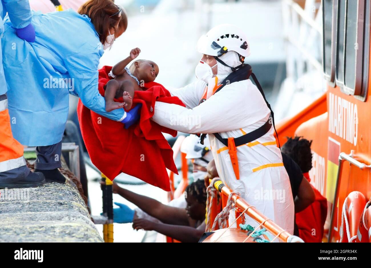 I soccorritori aiutano un bambino migrante a sbarcare da una nave di guardia costiera spagnola, nel porto di Arguineguin, nell'isola di Gran Canaria, Spagna, 26 agosto 2021. REUTERS/Borja Suarez Foto Stock