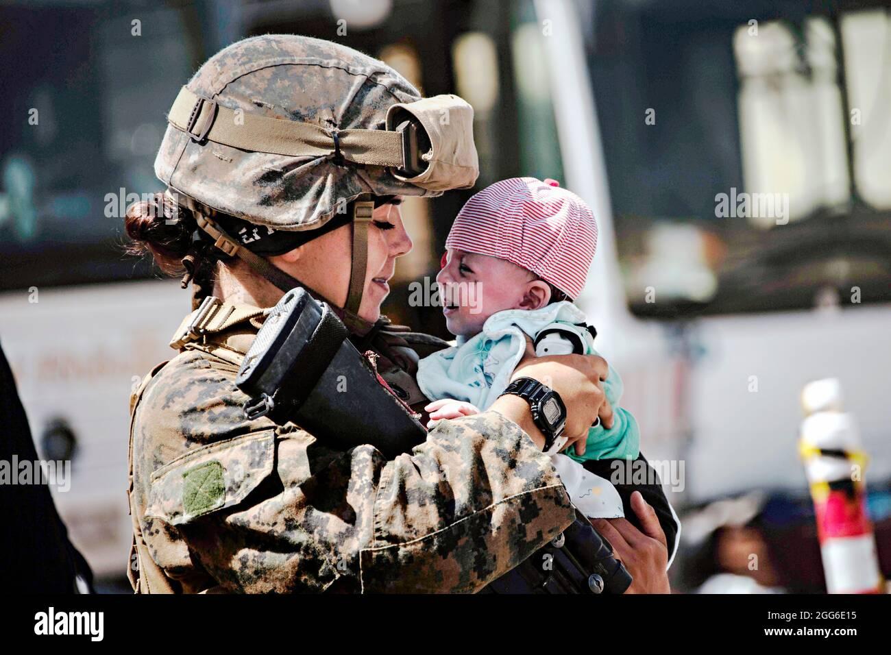Kabul, Afghanistan. 28 agosto 2021. Una Marina degli Stati Uniti con la 24a unità di spedizione marittima calma un bambino in attesa di evacuazione presso l'aeroporto internazionale Hamid Karzai durante l'operazione Rifuge Allees 28 agosto 2021 a Kabul, Afghanistan. Credit: Planetpix/Alamy Live News Foto Stock