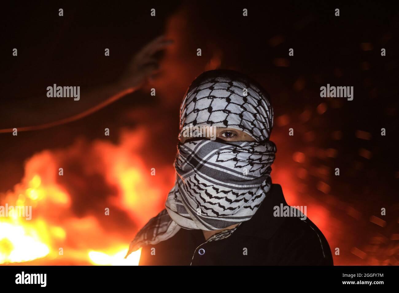 31 agosto 2021, campo profughi di Bureij, striscia di Gaza, Palestina: Dimostranti palestinesi durante gli scontri con i soldati israeliani lungo il confine tra la striscia di Gaza e Israele, ad est del campo profughi di Bureij, striscia di Gaza. Agosto 30, 2021. Nelle scorse settimane i manifestanti palestinesi hanno organizzato manifestazioni di massa nei pressi della barriera di confine per protestare contro il blocco israeliano. Decine di palestinesi sono stati feriti e due sono stati uccisi dal fuoco israeliano durante le proteste. (Credit Image: © Mahmoud Khattab/Quds Net News via ZUMA Press Wire) Foto Stock