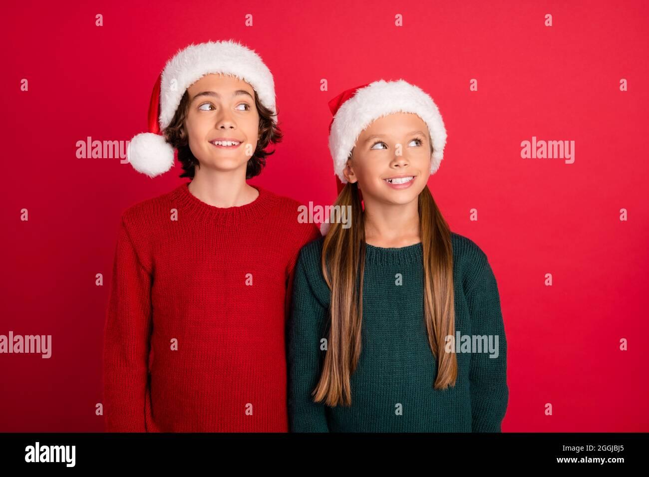Ritratto di due amici allegri e attraenti che indossano un cappellino festale che fantasiizza isolato su sfondo rosso brillante Foto Stock