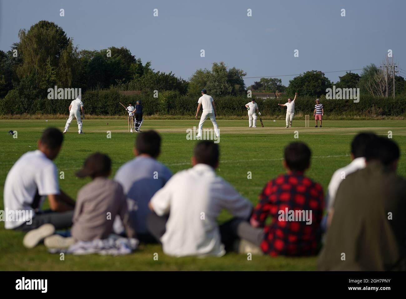 Sono arrivati di recente i cittadini afghani che guardano durante una partita di cricket con i membri del Newport Pagnell Town Cricket Club nel Buckinghamshire, organizzato dal club come un gesto di benvenuto nel Regno Unito. Data foto: Domenica 5 settembre 2021. Foto Stock