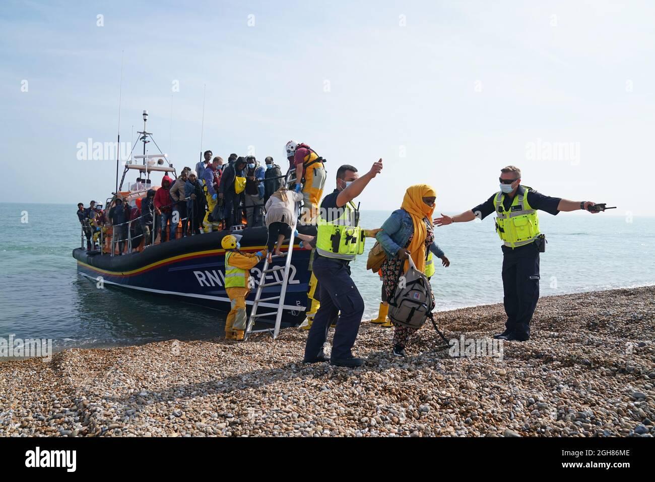 Un gruppo di persone che si pensa siano migranti viene portato a terra dalla barca di salvataggio locale a Dungeness nel Kent, dopo essere stato prelevato a seguito di un piccolo incidente in barca nella Manica. Data foto: Lunedì 6 settembre 2021. Foto Stock