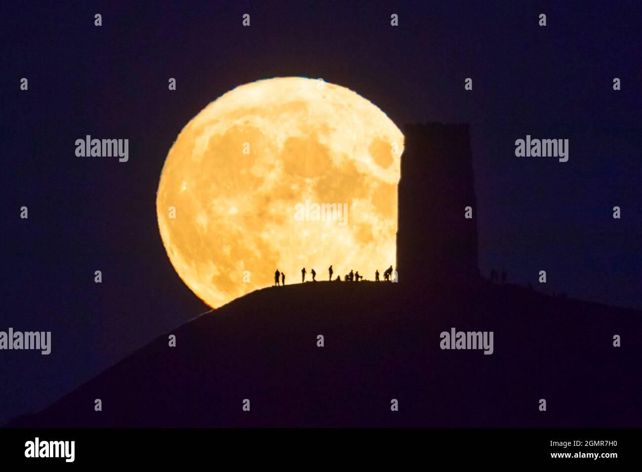 Glastonbury, Somerset, Regno Unito. 20 settembre 2021. Meteo Regno Unito. L'intera Harvest Moon si innalza nel cielo notturno chiaro da dietro la St Michael's Tower a Glastonbury Tor, nel Somerset che silhouette le persone in cima. Picture Credit: Graham Hunt/Alamy Live News Foto Stock