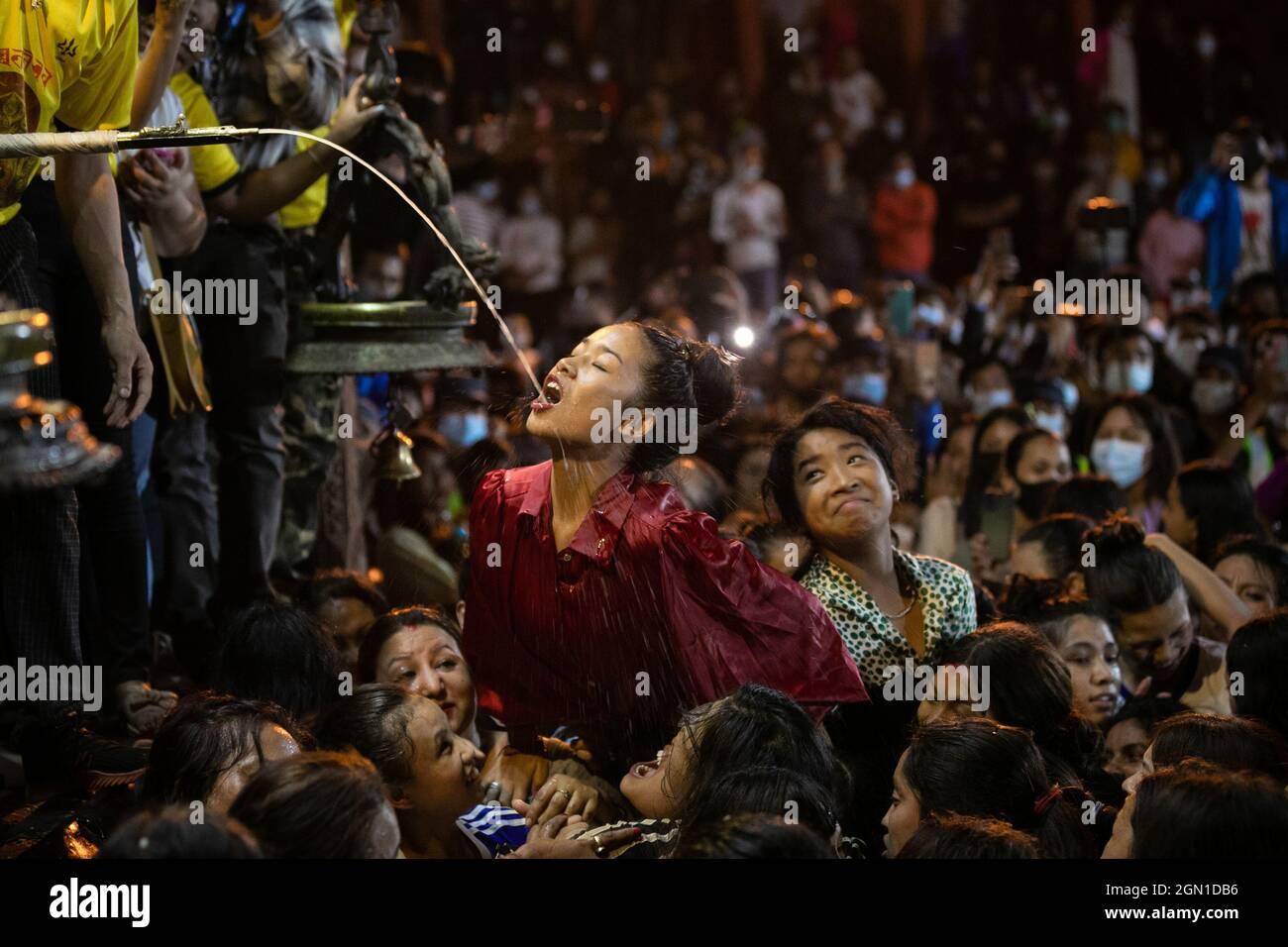 Kathmandu, Nepal. 21 settembre 2021. Le donne nepalesi lottano per bere l'alcool fatto in casa dalla bocca della divinità Swet Bhairav come benedizioni durante Indra Jatra festival.The festival annuale, chiamato dopo Indra, il dio della pioggia e del cielo, è celebrato da adorazione, gioire, cantare, ballare e feste nella valle di Kathmandu per segnare la fine della stagione monsone. Indra, la dea vivente Kumari e altre divinità sono adorate durante il festival. Credit: SOPA Images Limited/Alamy Live News Foto Stock