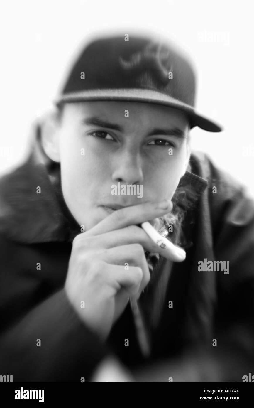 Giovane uomo che indossa cappello da baseball di fumare ritratto da vicino  Immagini Stock 5c12c97030a9
